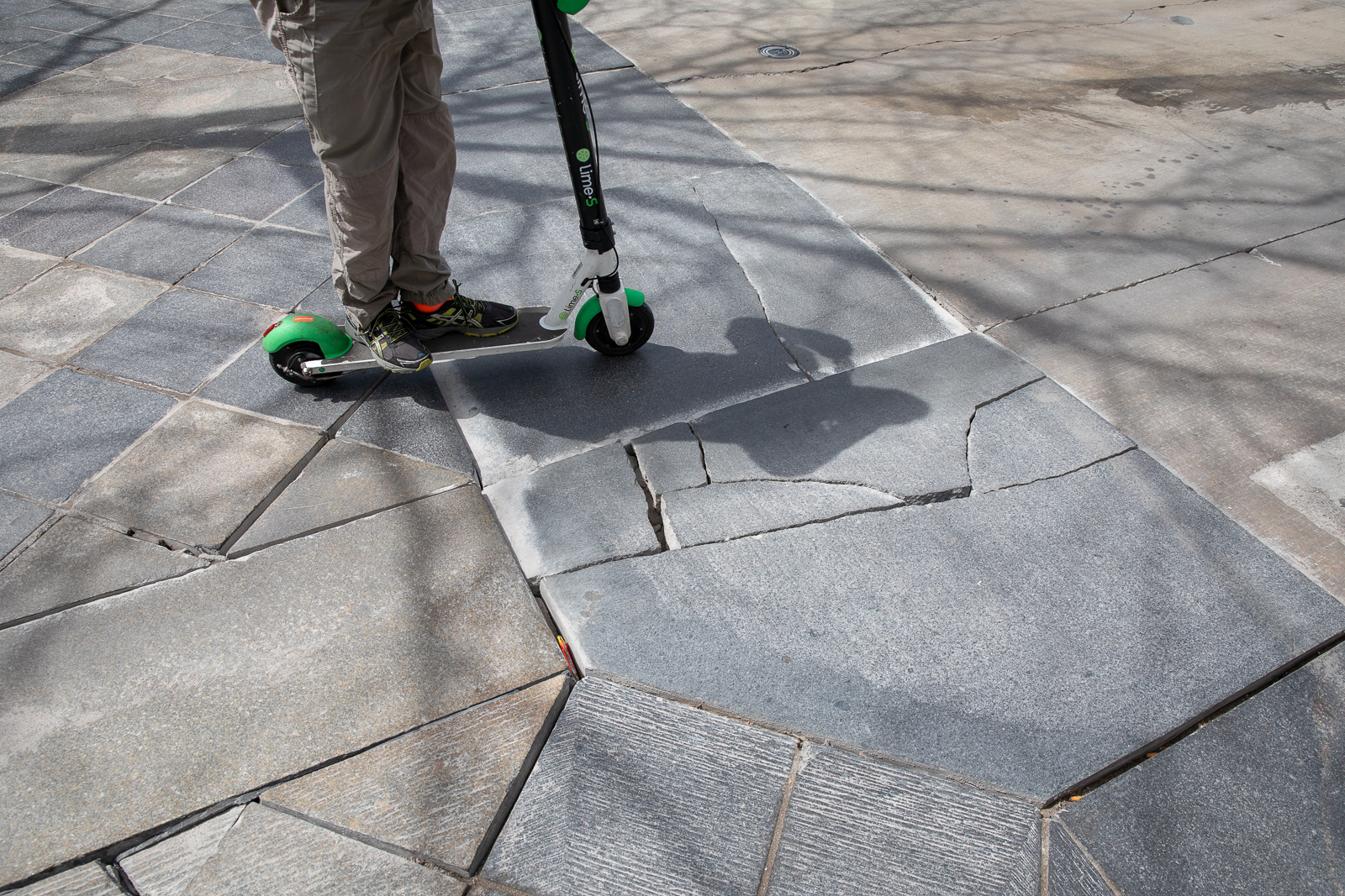 A scooter user passes around cracked and displaced tile on the 16th St. Mall. Photo: Andy Bosselman