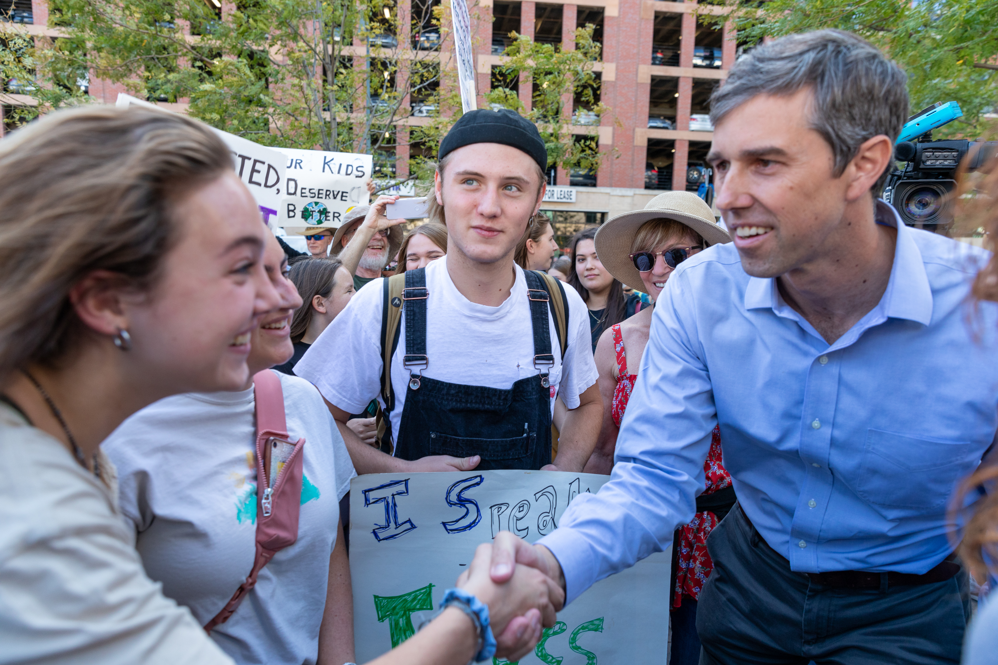 Presidential candidate Beto O'Rourke shakes hands with a youth protestor at Union Station.